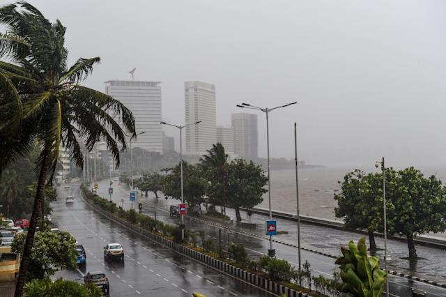 Motorists drive on a road near the Marine Drive under heavy rain in Mumbai on June 3, 2020. (Photo by PUNIT PARANJPE/AFP via Getty Images)