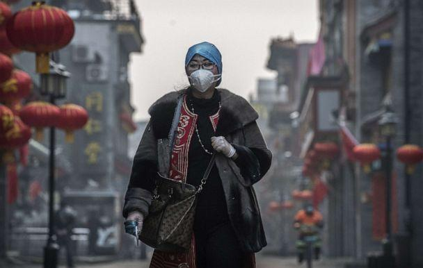 PHOTO: A Chinese woman wears a protective mask and gloves as she walks in a nearly empty and shuttered commercial street on Feb. 12, 2020 in Beijing. (Kevin Frayer/Getty Images)