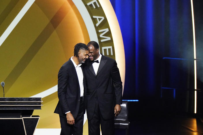 Tim Duncan, left, smiles with presenter David Robinson after being enshrined with the 2020 Basketball Hall of Fame class Saturday, May 15, 2021, in Uncasville, Conn. (AP Photo/Kathy Willens)