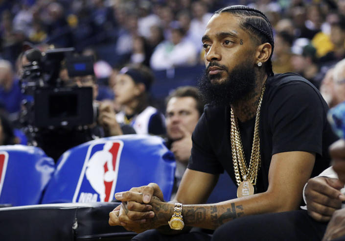 FILE - In this March 29, 2018, file photo, rapper Nipsey Hussle watches an NBA basketball game between the Golden State Warriors and the Milwaukee Bucks in Oakland, Calif. Hussle has been shot and killed outside his Los Angeles clothing store, Los Angeles Mayor Eric Garcetti said March 31, 2019. He was 33. (AP Photo/Marcio Jose Sanchez, File)