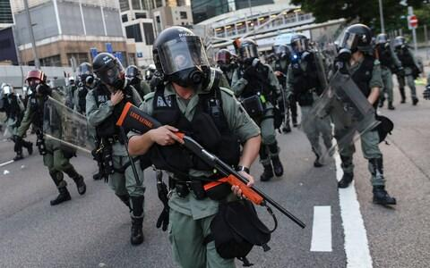 Armed Riot police officers on patrol during an anti-government rally - Credit: JEROME FAVRE/EPA-EFE/REX