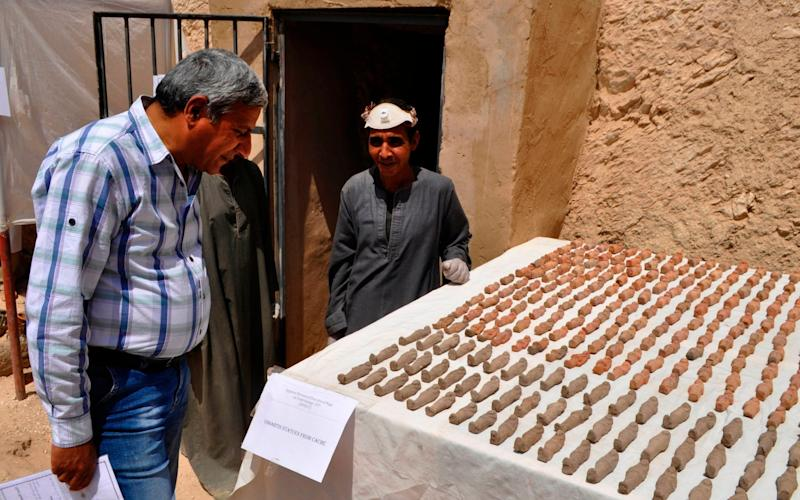 A member of an Egyptian archaeological team stands near artifacts discovered in a 3,500-year-old tomb in the Draa Abul Nagaa necropolis, near the southern city of Luxor, on April 18, 2017