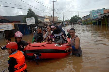 Rescue workers push an inflatable boat as they evacuate residents following floods in Makassar, South Sulawesi, Indonesia, January 23, 2019 in this photo taken by Antara Foto. Antara Foto/Abriawan Abhe/ via REUTERS