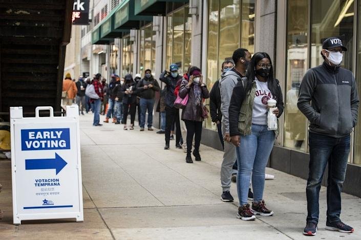 In this Oct. 1, 2020, file photo, hundreds of people wait in line to early vote in Chicago. (Ashlee Rezin Garcia/Chicago Sun-Times via AP, File)