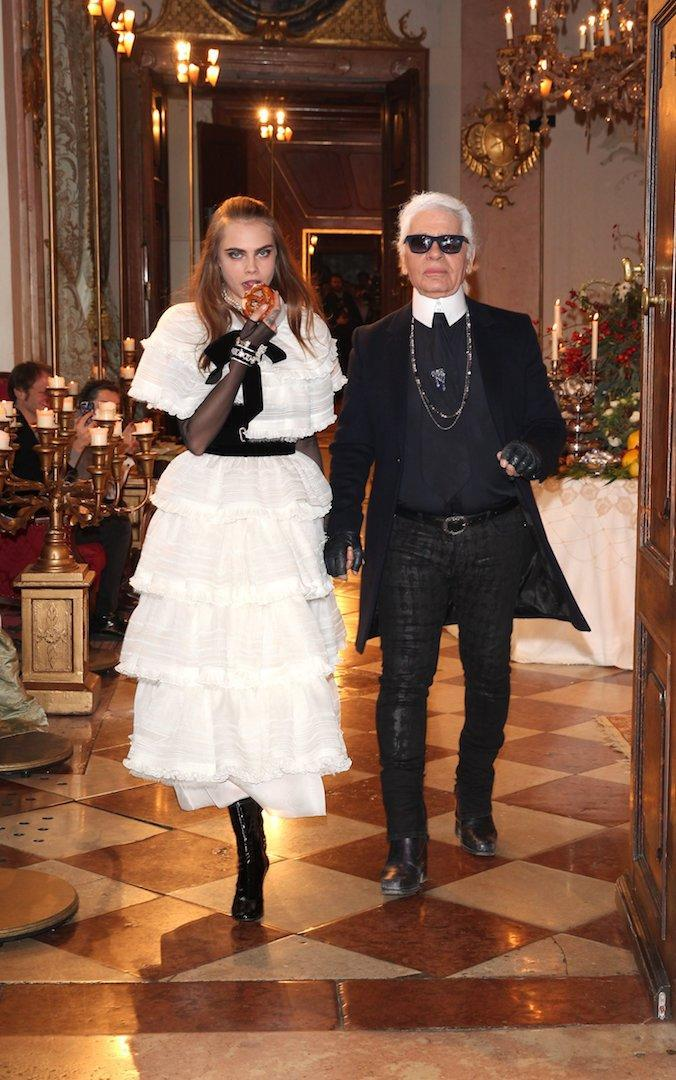 <p>The designer walks the runway with model Cara Delevigne following the Chanel Metiers d'Art Collection 2014/15 show in 2014. <em>[Photo: Getty]</em> </p>