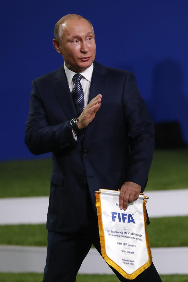 Russian President Vladimir Putin waves as he walks off stage at the FIFA congress on the eve of the opener of the 2018 soccer World Cup in Moscow, Russia, Wednesday, June 13, 2018. The congress in Moscow is set to choose the host or hosts for the 2026 World Cup. (AP Photo/Pavel Golovkin)