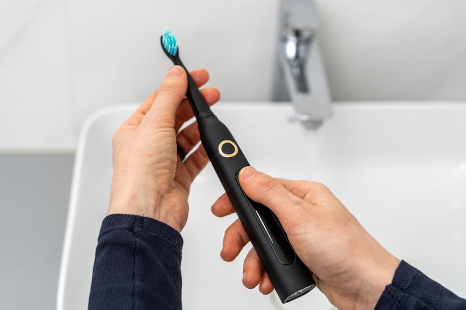Pov woman hold professional sonic electric toothbrush with replaceable brush in hands over sink on blurred background. Wireless equipment and oral care concept