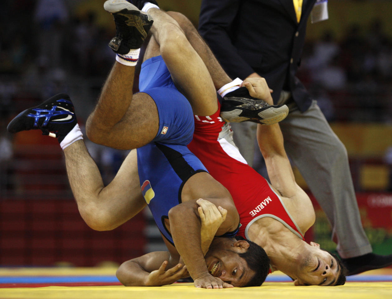 Abbas Dabbaghi, of Iran, in red, wrestles Fredy Serrano, of Columbia, in 55 kilogram category of men's freestyle wrestling competition of the Beijing 2008 Olympics in Beijing, Tuesday, Aug. 19, 2008.  (AP Photo/Saurabh Das )