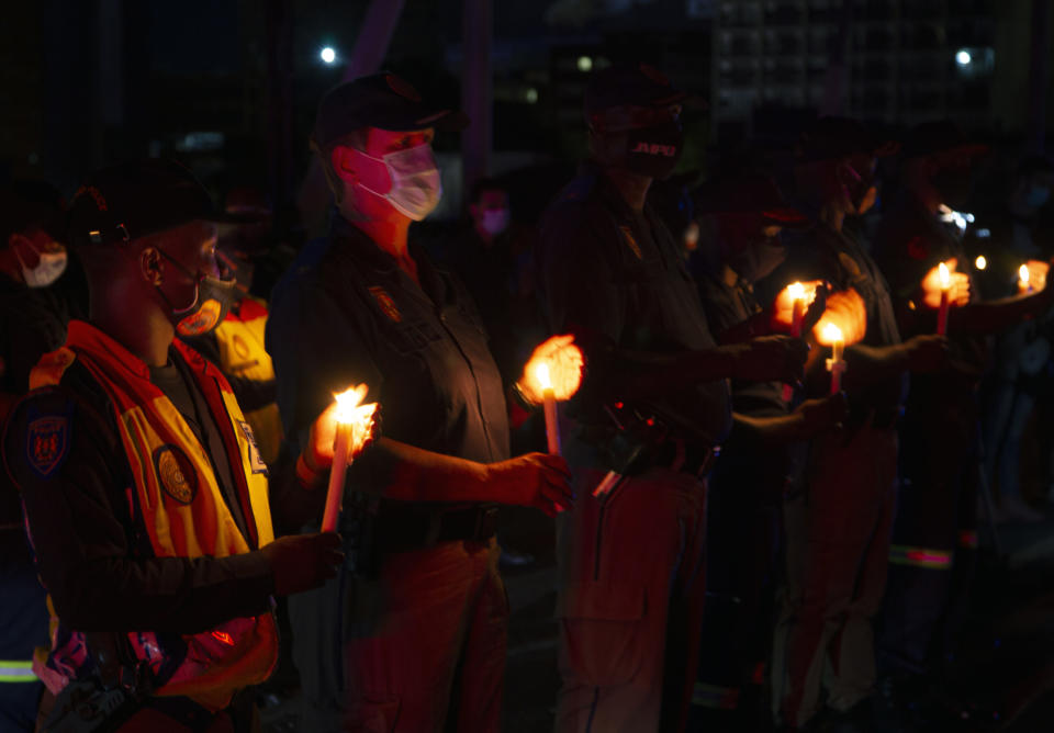 Frontline workers attend a candlelight ceremony on New Year's Eve on the famed Nelson Mandela Bridge in downtown Johannesburg Thursday, Dec. 31, 2020. Many South Africans will swap firecrackers for candles to mark New Year's Eve amid COVID-19 restrictions including a nighttime curfew responding to President Cyril Ramaphosa's call to light a candle to honor those who have died in the COVID-19 pandemic and the health workers who are on the frontline of battling the disease.. (AP Photo/Denis Farrell)