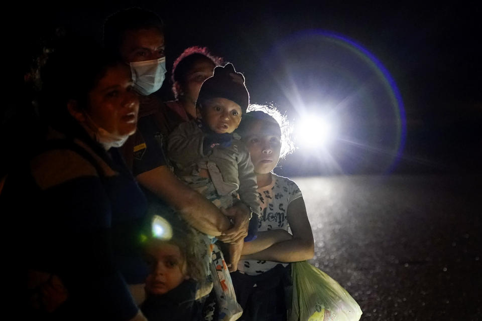 FILE - In this May 17, 2021, file photo a group of migrants mainly from Honduras and Nicaragua wait along a road after turning themselves in upon crossing the U.S.-Mexico border, in La Joya, Texas. The Biden administration says families arriving at the U.S. border with Mexico will have their cases fast-tracked in immigration court, an announcement Friday, May 28, that comes less than two weeks after said it was easing pandemic-related restrictions on seeking asylum. Under the plan, immigration judges in 10 cities will aim to decide cases within 300 days. (AP Photo/Gregory Bull, File)