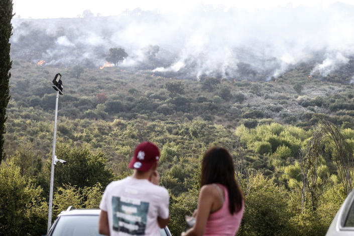 People watch as a fire burns on Castillo mountain park near Tivoli a few miles from Rome, Italy, Friday, Aug. 13, 2021. Intense heat baking Italy pushed northward towards the popular tourist destination of Florence Friday while wildfires charred the country's south, and Spain appeared headed for an all-time record high temperature as a heat wave kept southern Europe in a fiery hold. (Cecilia Fabiano/LaPresse via AP)