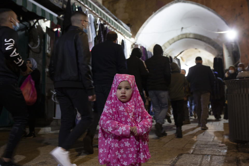 A Palestinian toddler wears a jilbab, an Islamic garment, on the eve of the Muslim holy month of Ramadan in the Old City of Jerusalem, Monday, April 12, 2021. (AP Photo/Maya Alleruzzo)