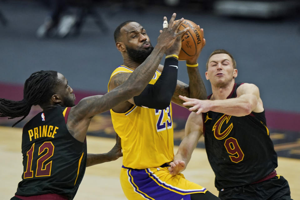 Los Angeles Lakers' LeBron James (23) drives to the basket between Cleveland Cavaliers' Taurean Prince (12) and Dylan Windler (9) in the second half of an NBA basketball game, Monday, Jan. 25, 2021, in Cleveland. The Lakers won 115-108. (AP Photo/Tony Dejak)