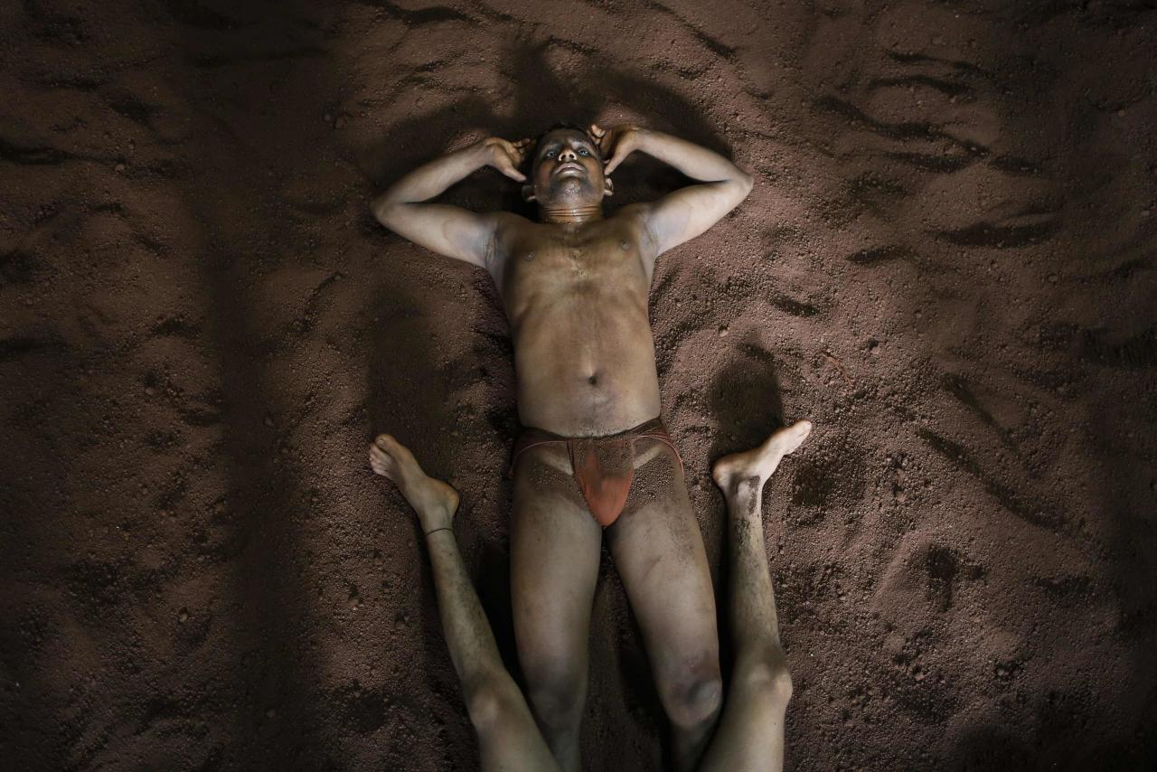 Wrestlers exercise before practising in the mud at a traditional Indian wrestling centre called Akhaara in Mumbai March 4, 2014. Kushti (mud wrestling) is a traditional sport in India but more and more young athletes are now training to wrestle on mats instead of mud to gain access to top international competitions like the Olympic Games or the Commonwealth Games. REUTERS/Danish Siddiqui (INDIA - Tags: SOCIETY SPORT)