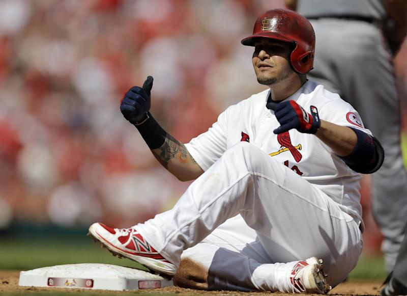 St. Louis Cardinals' Yadier Molina celebrates as he looks into the dugout after hitting a two-run single during the fourth inning of a baseball game against the Washington Nationals Wednesday, Sept. 25, 2013, in St. Louis. (AP Photo/Jeff Roberson)