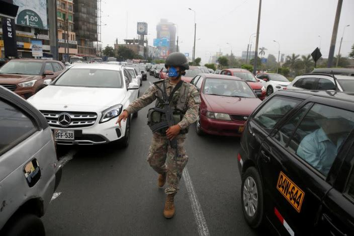 A soldier checks drivers' documents after Peru's government deployed military personnel to block major roads, as the country rolled out a 15-day state of emergency to slow the spread of coronavirus disease (COVID-19), in Lima