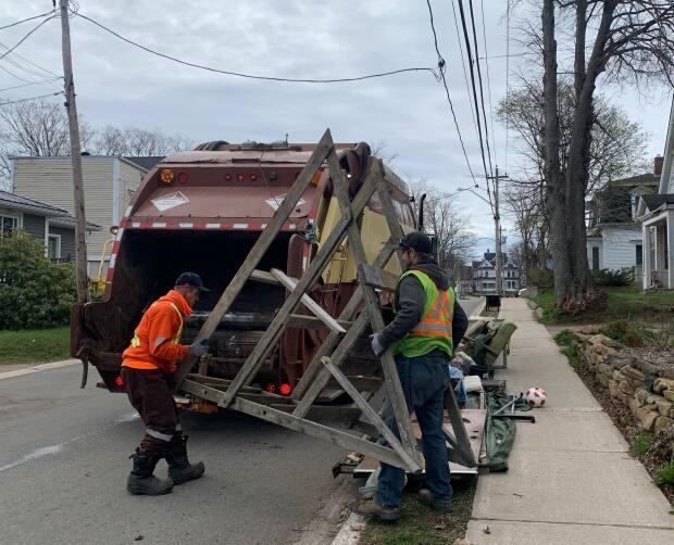 The junk left curbside during large pick up is put in the truck by hand. Acton reminds people to make sure there aren't nails sticking out of boards, and the material isn't dangerous to move for the company employees.