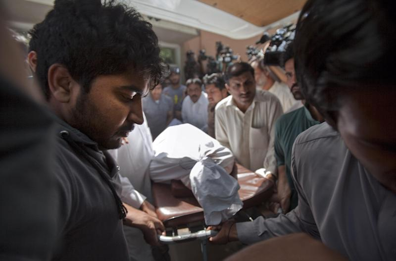 Family members and relatives of Pakistani prosecutor Chaudhry Zulfikar who was assassinated hours earlier, load his body into an ambulance from a morgue in Islamabad, Pakistan, Friday, May 3, 2013. Gunmen killed Pakistan's lead prosecutor investigating the assassination of former prime minister Benazir Bhutto as he drove to court in the capital on Friday, throwing the case that also involves former ruler Pervez Musharraf into disarray. (AP Photo/Anjum Naveed)
