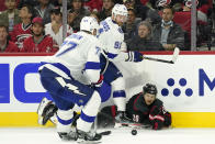 Carolina Hurricanes center Sebastian Aho (20) falls to the ice while chasing the puck with Tampa Bay Lightning defenseman Victor Hedman (77) and center Steven Stamkos (91) during the second period in Game 1 of an NHL hockey Stanley Cup second-round playoff series in Raleigh, N.C., Sunday, May 30, 2021. (AP Photo/Gerry Broome)