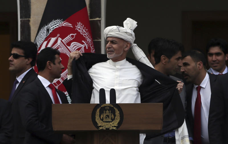 Afghan President Ashraf Ghani, center, opens his coat after a few rockets are fired during his speech after being sworn, at his inauguration ceremony at the presidential palace in Kabul, Afghanistan, Monday, March 9, 2020. To reassure his supporters, Ghani threw open his jacket saying he wasn't even wearing a bullet proof vest. (AP Photo/Rahmat Gul)