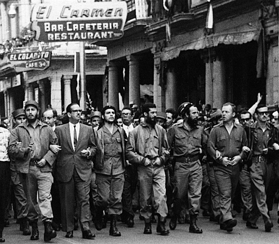"""<p>Cuban leaders walk arm-in-arm at the head of the March 5, 1960 funeral procession for the victims of the La Coubre explosion, blamed by the Cuban government on a U.S. bomb attack on the Cuban ship La Coubre in the harbor of Havana. From left to right are Fidel Castro; the first president of post-Batista Cuba, Osvaldo Dortico; Ernesto """"Che"""" Guevara; Defense Minister Augusto Martinez-Sanchez; Ecology Minister Antonio Nunez-Jimenez; American William Morgan from Toledo, Ohio; and Spaniard Eloy Gutierrez Menoyo. Morgan became a Cuban sympathizer after a friend was reportedly killed by President Batista's police. He was later executed in 1961, accused of being anti-Communist. Menoyo later founded the anti-Castro Alfa 66 organization. (AP Photo) </p>"""