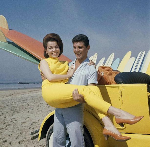 "FILE - In this 1963 file photo, singer Frankie Avalon and actress Annette Funicello are seen on Malibu Beach during filming of ""Beach Party,"" in California in 1963. Funicello helped create a world as fanciful as Walt Disney's Magic Kingdom when she traded in her Mousketeer ears for a modest one-piece bathing suit . It was a land of perfect waves and sparkling sand, in a place where there was a beach party every night and summer never ended. (AP Photo/File)"