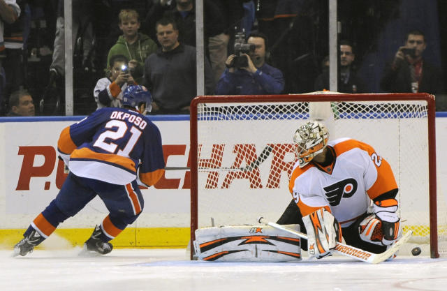 New York Islanders' Kyle Okposo (21) shoots the puck past Philadelphia Flyers goalie Ray Emery (29) to score the final goal in a shootout of an NHL hockey game on Monday, Jan. 20, 2014, in Uniondale, N.Y. The Islanders won 4-3. (AP Photo/Kathy Kmonicek)