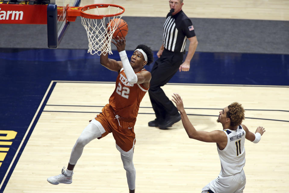Texas forward Kai Jones (22) shoots while defended by West Virginia forward Emmitt Matthews Jr. (11) during the second half of an NCAA college basketball game Saturday, Jan. 9, 2021, in Morgantown, W.Va. (AP Photo/Kathleen Batten)