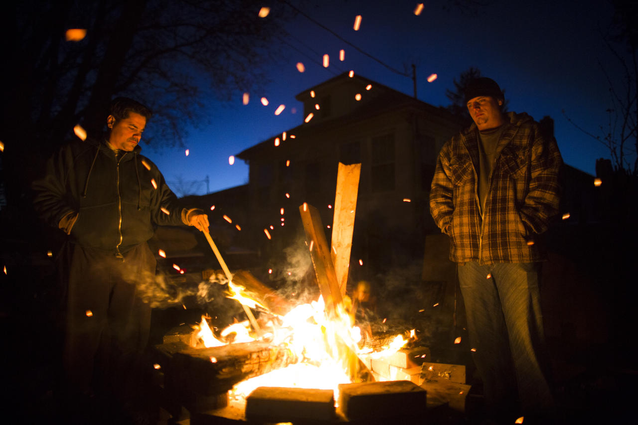 Frank d'Amico, 46, left, and Orlando Vogler, 26, stand by their fire pit to keep warm after their homes in the New Dorp Beach were devastated by Superstorm Sandy, Monday, Nov. 5, 2012, in the Staten Island borough of New York. Although many areas of the metropolitan area are beginning to return to normal, neighborhoods of Staten Island's southern shore remain without power as the cleanup continues. (AP Photo/John Minchillo)