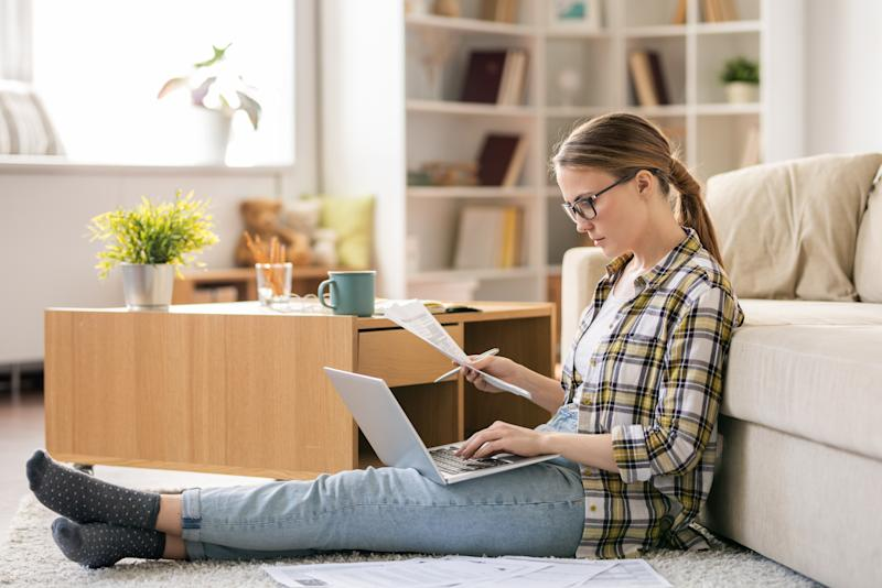 Serious concentrated young woman in glasses sitting on floor in living room and using laptop while checking bills at home