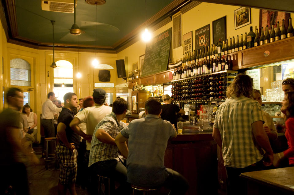 Photo shows a group of people sitting and standing around a bar. Source: Getty Images