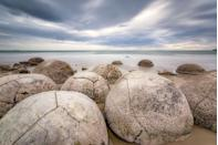 "<p>Home to almost perfectly spherical boulders, this beach resembles a carton full of stone eggs. Formed roughly <a href=""https://www.newzealand.com/us/feature/moeraki-boulders/"" rel=""nofollow noopener"" target=""_blank"" data-ylk=""slk:65 million"" class=""link rapid-noclick-resp"">65 million</a> years ago, these calcite boulders are legendary. No, really, they're central to a Maori legend of a disastrous canoe voyage. </p>"
