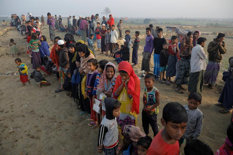 Rohingya refugees wait for a rice delivery at a Bangladesh camp in December.  (Marko Djurica / Reuters)