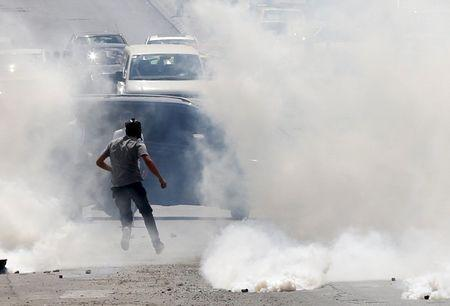 A Palestinian protester runs from tear gas fired by Israeli troops during clashes in the occupied West Bank city of Bethlehem, September 21, 2015. REUTERS/Ammar Awad