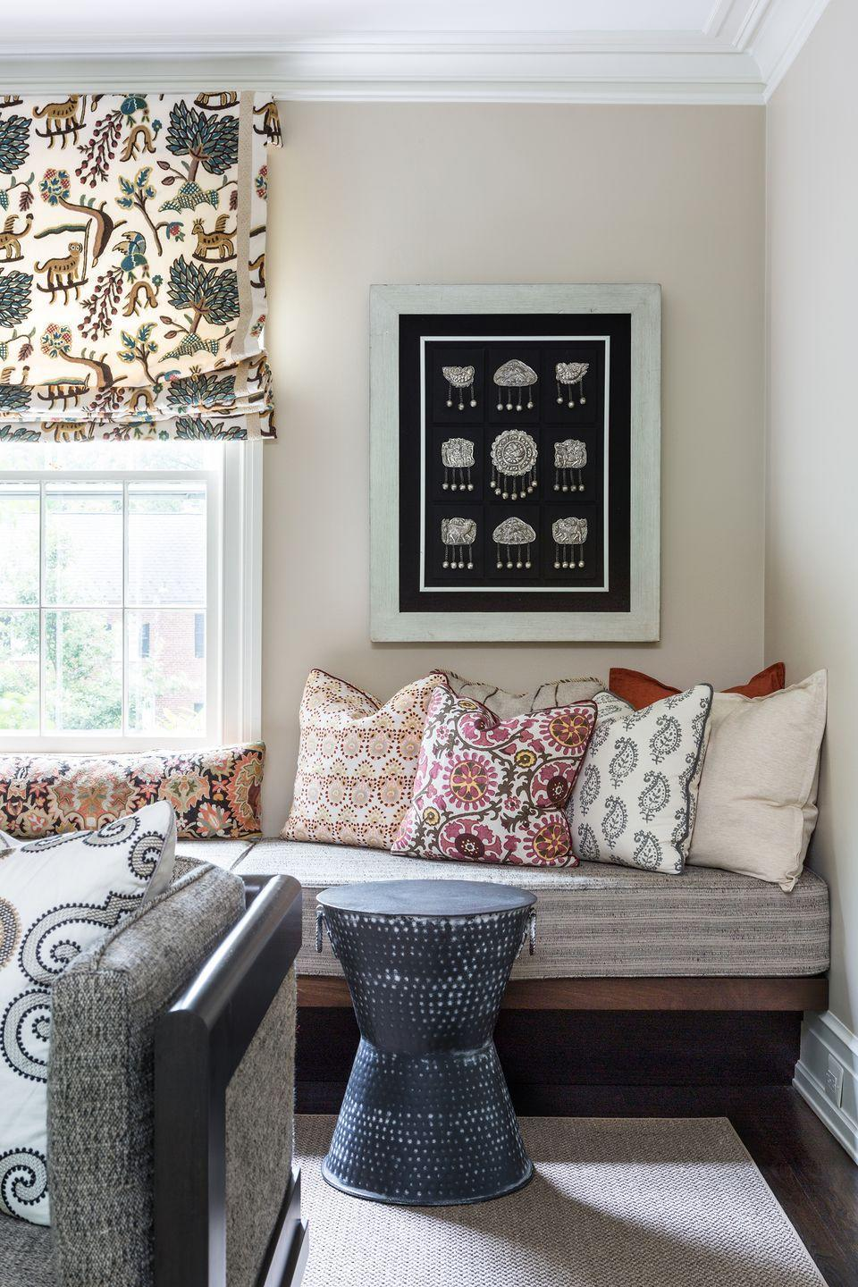"""<p>Layering accent pillows is a go-to fall decor trick for designer <a href=""""https://meyerinteriors.com/"""" rel=""""nofollow noopener"""" target=""""_blank"""" data-ylk=""""slk:Marika Meyer"""" class=""""link rapid-noclick-resp"""">Marika Meyer</a>, who is based in Washington, D.C. In this inviting living room, Marika paired a base of neutral throw pillows with patterned styles in warm terracotta hues. The pillows, which can be updated from season to season, also complement the fall-appropriate Roman shades.<br></p>"""