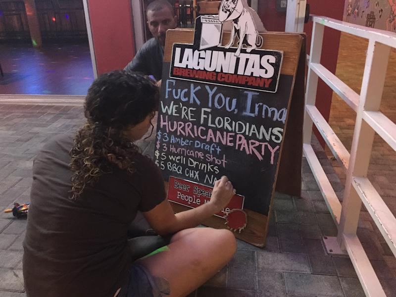 A bar employee in Fort Lauderdale scrawls a sign announcing a Hurricane Irma party. (Travis Waldron/HuffPost)