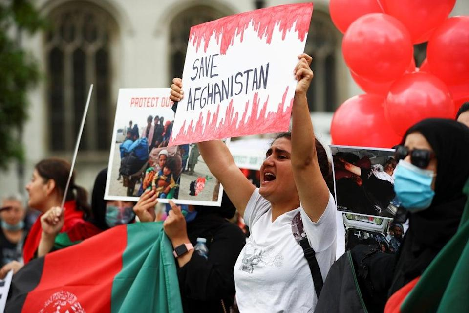 """Demonstrators hold """"save Afghanistan"""" banners in Parliament Square (REUTERS)"""