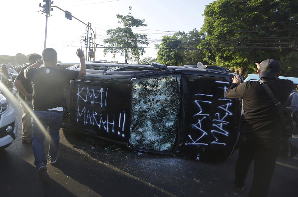 "Plain-clothed police officers secure the area where a government-owned car is overturned and vandalized by student protesters during a rally in Makassar, South Sulawesi province, Indonesia, Thursday, Sept. 26, 2019. Protests continue in several cities in the country as students rallied against a new law that critics say cripples the country's anti-corruption agency. Writings on the car read ""We are angry."" (AP Photo/Bahauddin Raja Baso)"