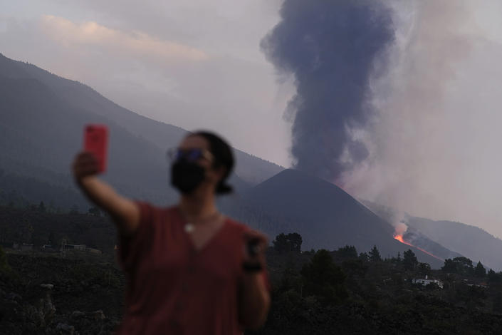 A woman takes a selfie as lava flows from a volcano on the Canary island of La Palma, Spain on Monday Sept. 27, 2021. A Spanish island volcano that has buried more than 500 buildings and displaced over 6,000 people since last week lessened its activity on Monday, although scientists warned that it was too early to declare the eruption phase finished and authorities ordered residents to stay indoors to avoid the unhealthy fumes from lava meeting sea waters. (AP Photo/Daniel Roca)