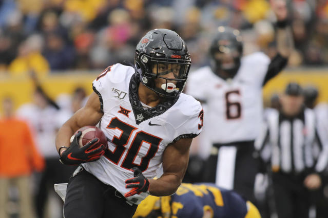 Oklahoma State's Chuba Hubbard (30) carries the ball during the second quarter of an NCAA college football game against West Virginia in Morgantown, W.Va., on Saturday, Nov. 23, 2019. (AP Photo/Chris Jackson)