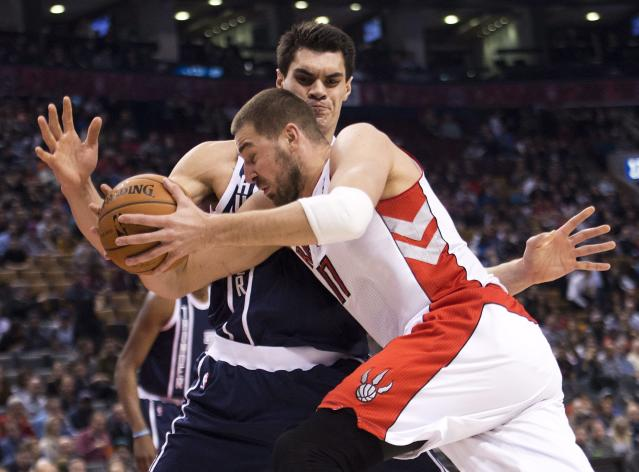 Toronto Raptors forward Jonas Valanciunas, front, tries to drive past Oklahoma Thunder forward Steven Adams during the first half of an NBA basketball game in Toronto on Friday, March 21, 2014. (AP Photo/The Canadian Press, Nathan Denette)