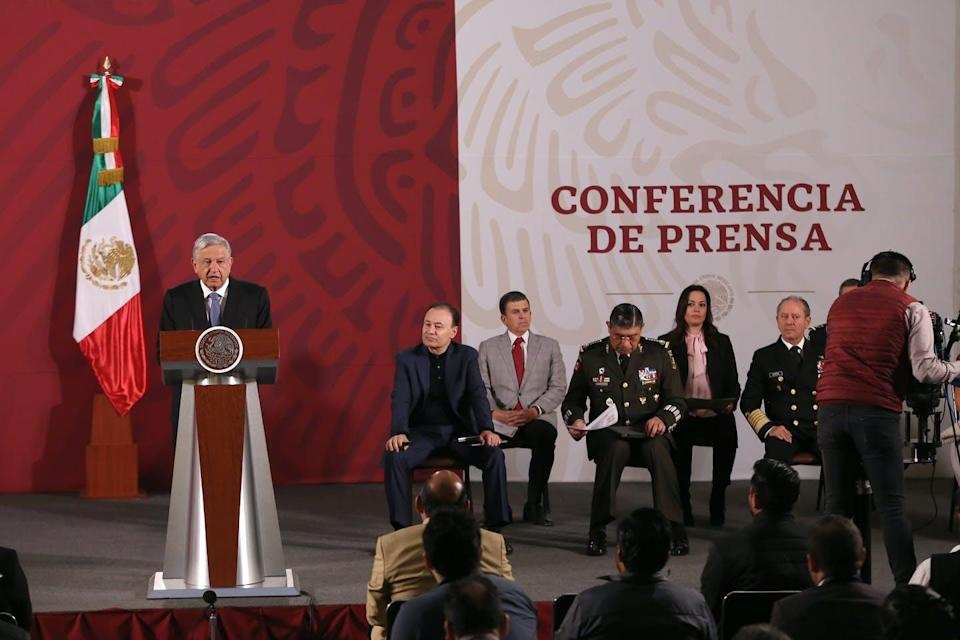 Mexico's president speaks at a lectern on a stage with a small crowd of government officials sitting nearby