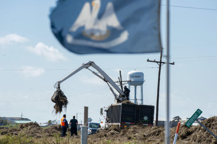 Terrebonne Parish solid waste crews remove marsh grass that washed across La. 56 in Cocodrie, La., during Hurricane Zeta, as residents slowly return to their homes and fishing camps to assess the damage on Thursday, October 29, 2020. (Chris Granger/The Advocate via AP)