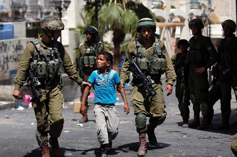Israeli soldiers arrest a young Palestinian boy following clashes in the West Bank town of Hebron on June 20, 2014 (AFP Photo/Thomas Coex)