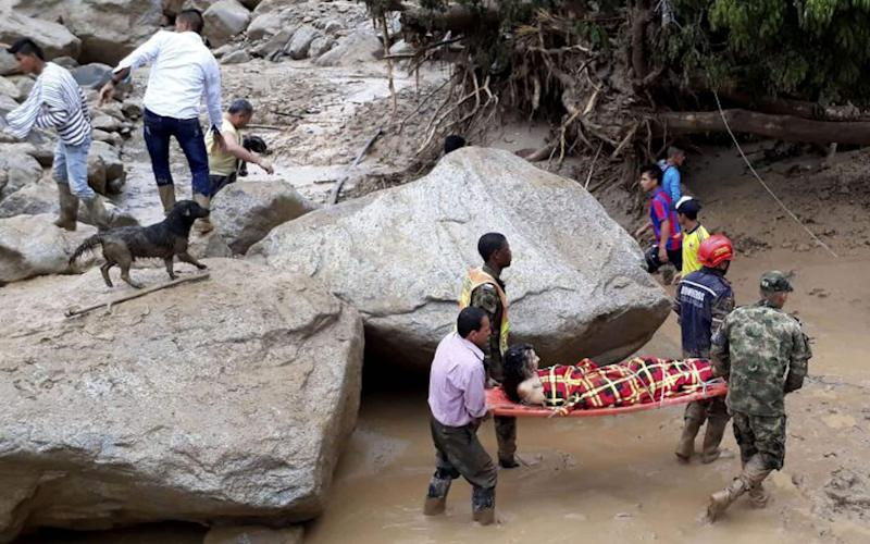 Rescuers carry a woman to safety - Credit: AFP