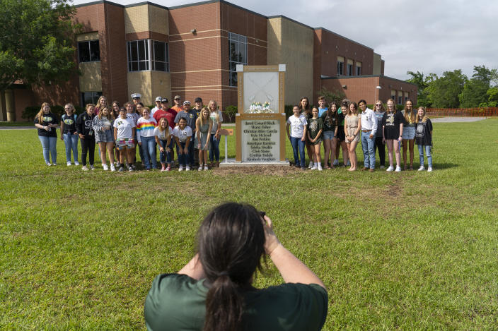 """Megan Grove, the chair of the Santa Fe Ten Memorial Foundation, takes a picture of current and former students around the new memorial to the ten victims of the 2018 mass shooting at the high school following a dedication ceremony, Tuesday, May 18, 2021, outside of the high school in Santa Fe, Texas. The Santa Fe Ten Memorial Foundation unveiled the """"Unfillable Chair,"""" a student designed memorial, on the third anniversary of the shooting. The foundation is planning a larger memorial for the future. (Mark Mulligan/Houston Chronicle via AP)"""
