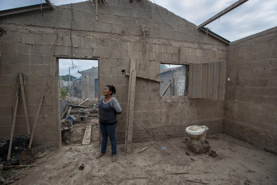Maria Elena Vasquez stands inside what's left of her home after last year's hurricanes Eta and Iota in La Lima, on the outskirts of San Pedro Sula, Honduras, where she returns every afternoon to remove the mud in hopes of returning to live here, Wednesday, Jan. 13, 2021. Twenty-two years before the 2020 storms, Hurricane Mitch destroyed Vasquez's other home, which was replaced with this one, built by a Catholic charity from Canada. (AP Photo/Moises Castillo)