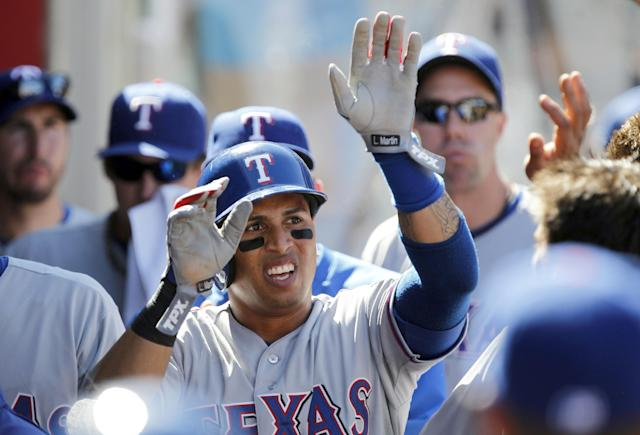 Texas Rangers' Leonys Martin, center, gets congratulations from the bench after scoring on a sacrifice fly against the Los Angeles Angels in the seventh inning during a baseball game, Sunday, Sept. 8, 2013, in Anaheim, Calif. (AP Photo/Alex Gallardo)