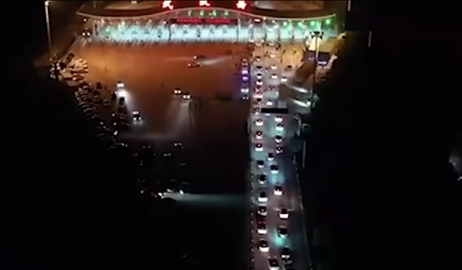 Cars queue up at toll gates to leave the city on Tuesday night. Source: People's Daily