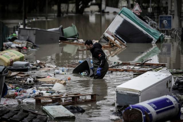 <p>A resident cleans debris from a flooded street in Villeneuve-Saint-Georges, south of Paris, on Jan. 25, 2018. (Photo: Philippe Lopez/AFP/Getty Images) </p>